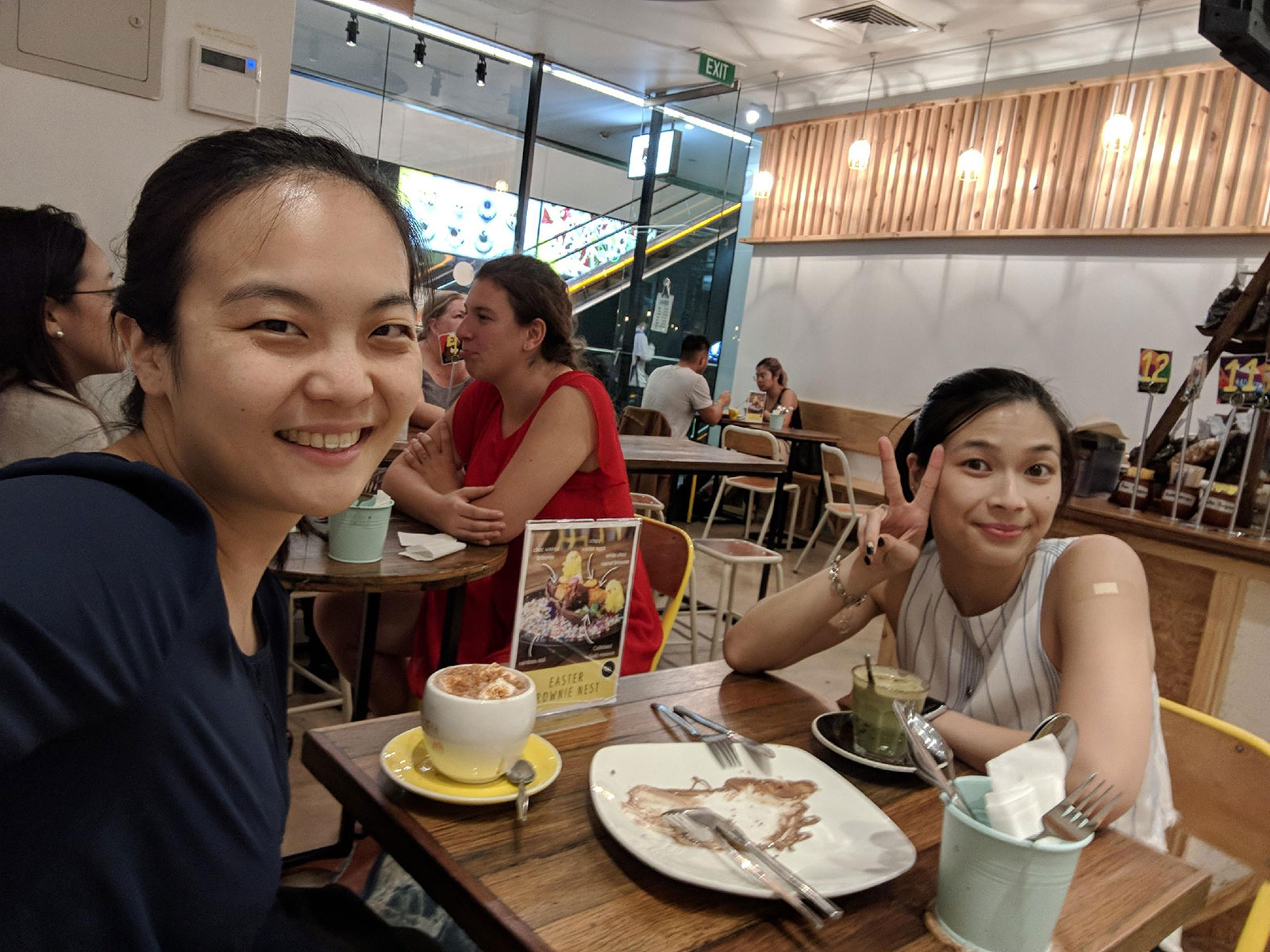 Two girls facing the camera, smiling. They are sitting at a table with two cups of hot drinks. The one further away from the camera is making a peace/victory sign with two fingers. In the middle of the table is a white plate with some chocolate sauce on it, and two sets of cutlery. They are in a cafe setting.