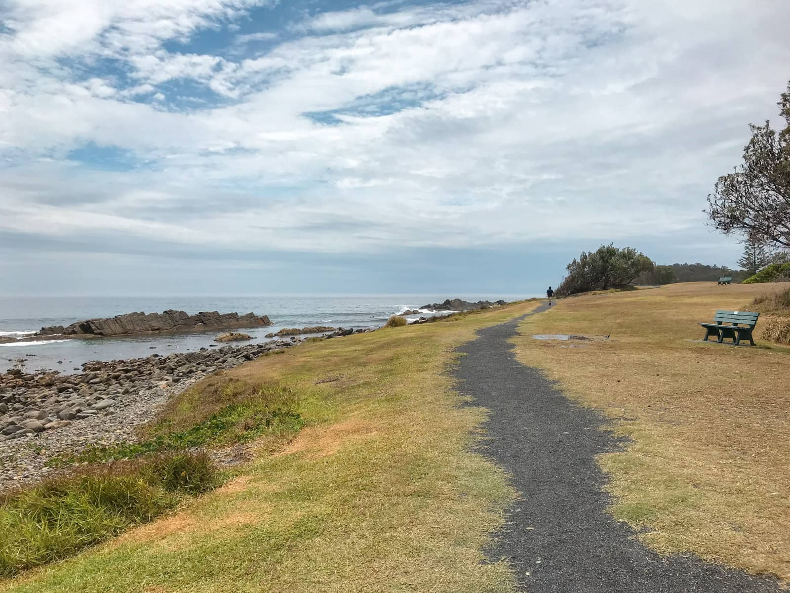 A grassy area with a grey gravel path leading into the distance. The path has ragged edges. On the left is a rocky beach leading to the sea, and on the right is a wooden bench in the foreground. A man can be seen walking on the path in the distance