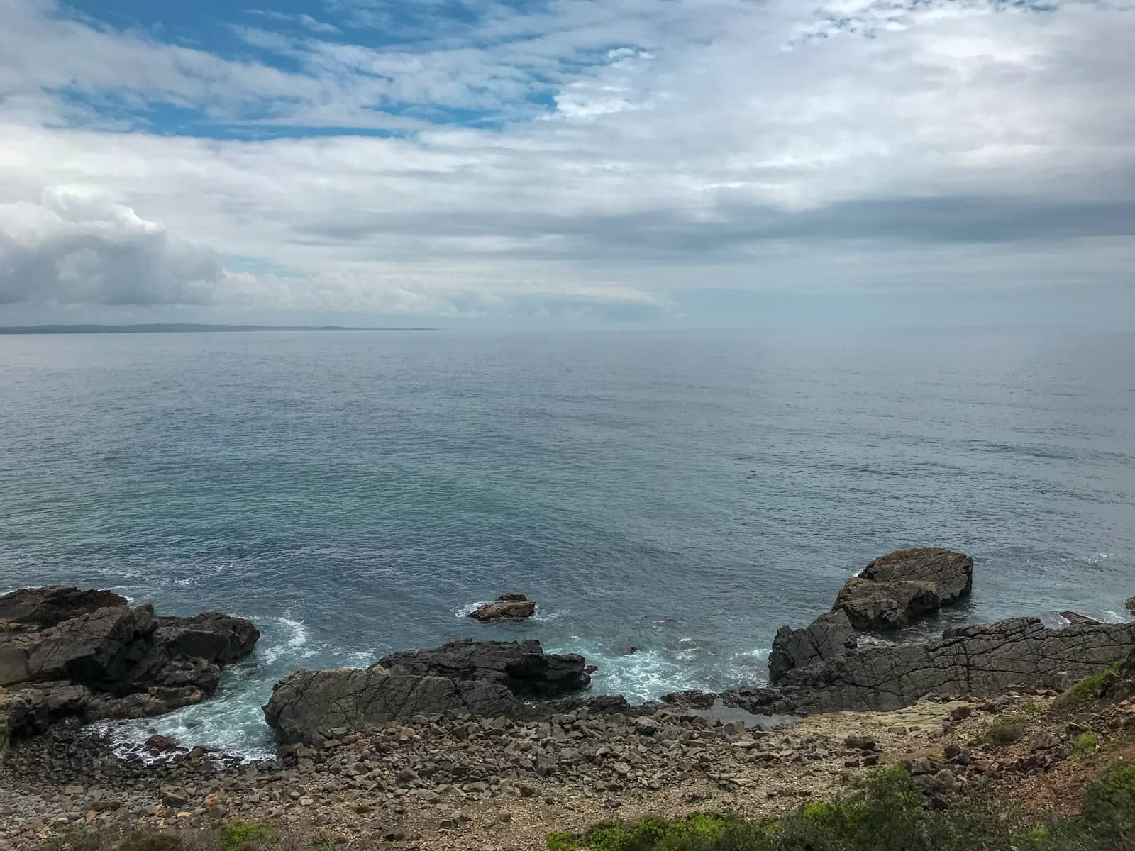 A view of the ocean, with a cloudy sky. In the foreground were some large rocks which are also partially immersed in the water.
