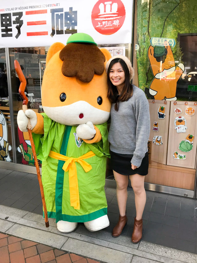 A girl in a grey jumper, black skirt and brown boots, smiling, alongside someone dressed in an animal costume. The animal is a bit like a cat with orange fur and white paws, and is wearing a bright green toga and small bright green cap.