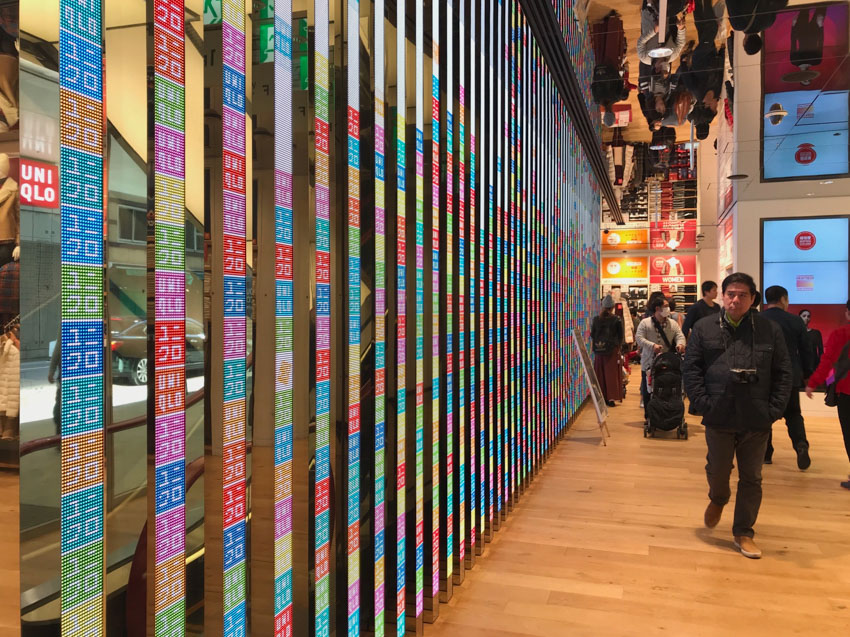 The inside of a store with wooden floors. Narrow reflective panels alternated with panels of columns of coloured squares make up a wall on the left. Some people are visible in the distance, not too close to the wall.