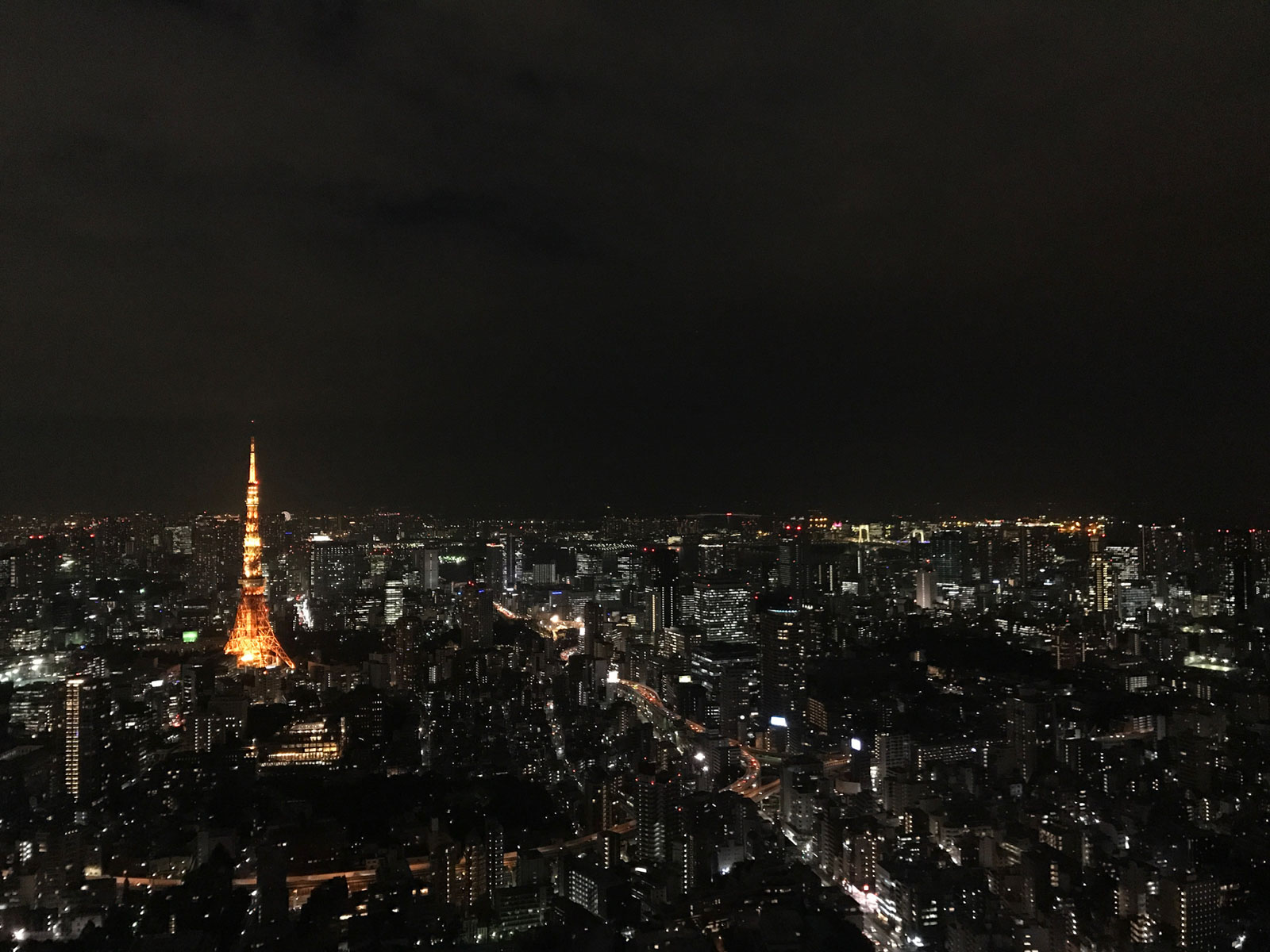 A city at night, with many buildings with lights on. One brightly lit tower with yellow lighting stands out amongst the other buildings