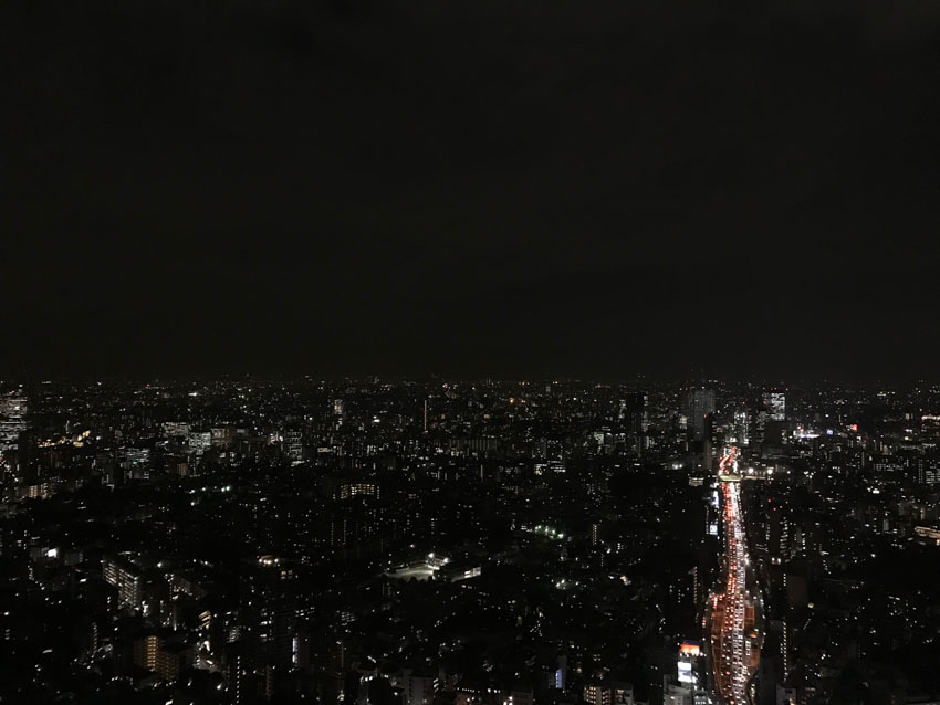 A wide view of a city at night from a high altitude. A long line of different coloured lights shows a road of traffic one side of the photo, moving into the distance.