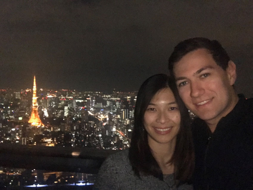 A girl with short dark hair, and boy with dark hair, smiling. It's nighttime and the lights are on in the buildings that are in the background. There is a tower that stands out with yellow/orange lights.