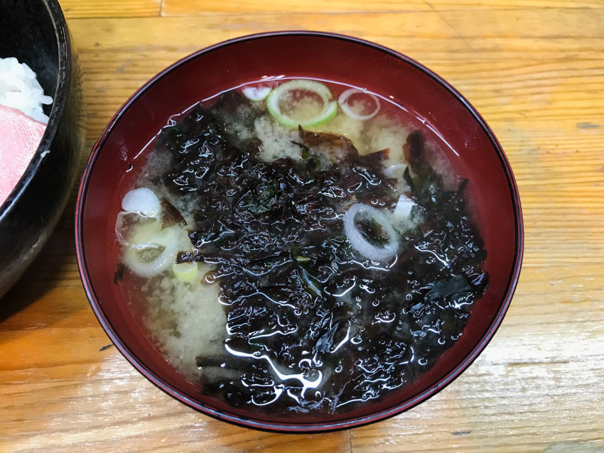 A bowl of cloudly soup with small green onions. There is a lot of dark green wet seaweed in the bowl.
