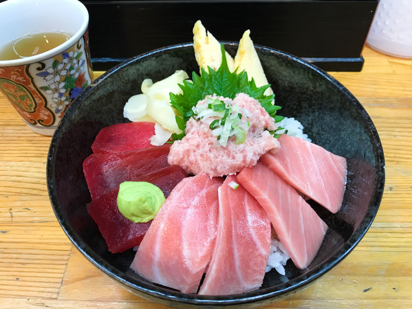 A black bowl containing rice with deep red and light pink slices of raw tuna. It's topped with a soft scoop of pink tuna, yellow pickled ginger, and a pea-sized piece of wasabi.