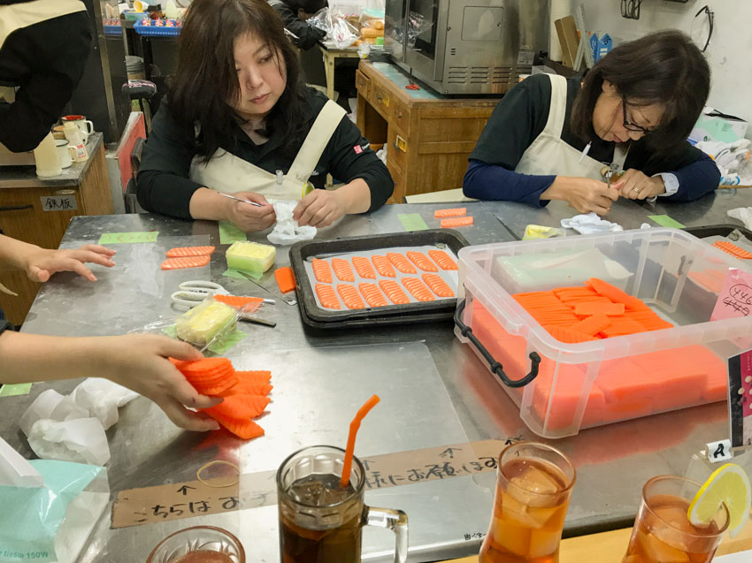 Some workers at Sample Kobo creating some raw salmon replicas by hand