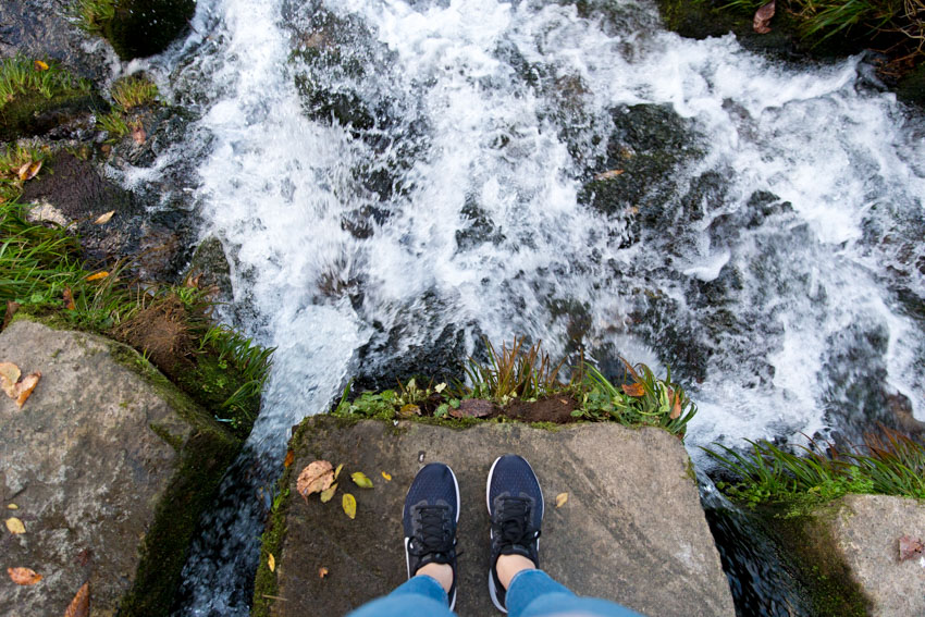 A bird's-eye view of my Nike shoes with the river splashing on the rocks around me and the rock I am standing on