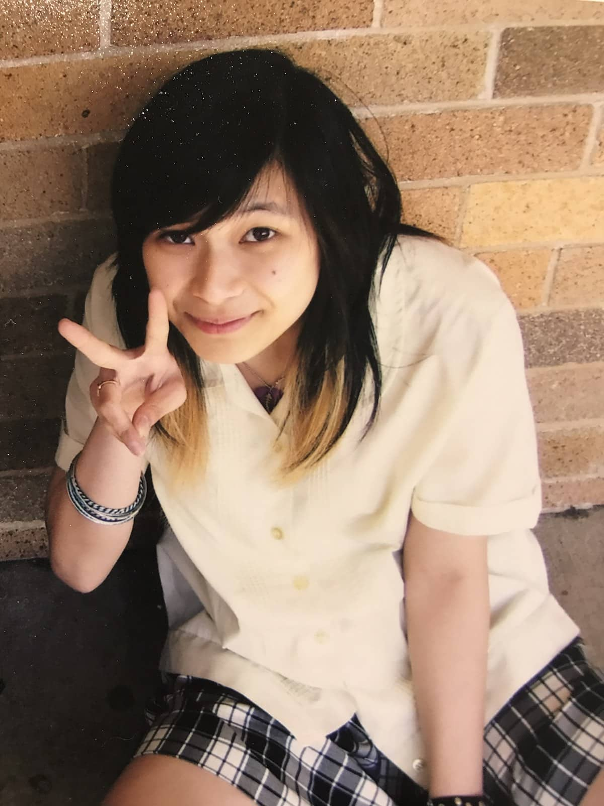 A girl in a school uniform holding her two fingers up in a peace sign. She has short dark hair with blonde ends
