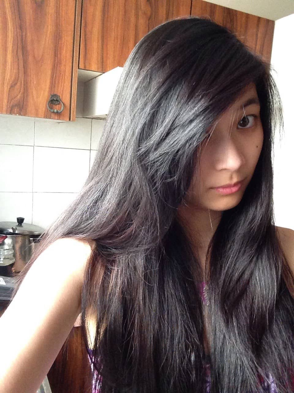 A girl taking a selfie with part of her long hair covering the side of her face. Her hair is black-purple in colour.