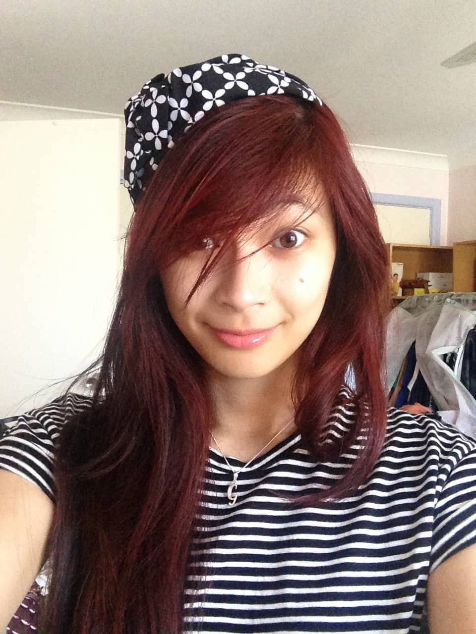 A woman with long red hair, taking a selfie. She has a black and white headband on and is wearing a black and white striped shirt.