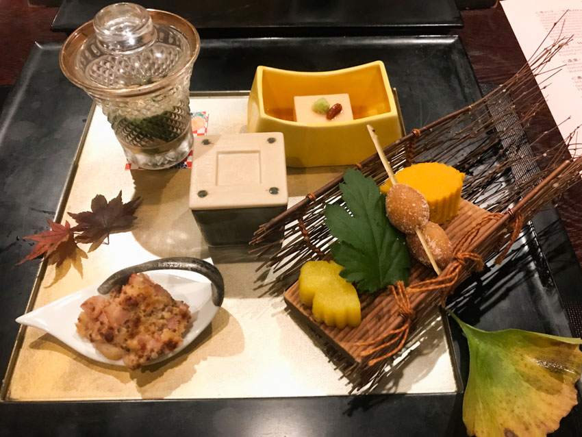 A tray of appetisers, one in a small glass with a lid, another in a square crucible with a lid, a square of tofu in a small rectangular cup, a leaf-shaped dish with an appetiser of shrimp with bacon and cheese, a small sled made of natural sticks with a couple of cakes and a skewer