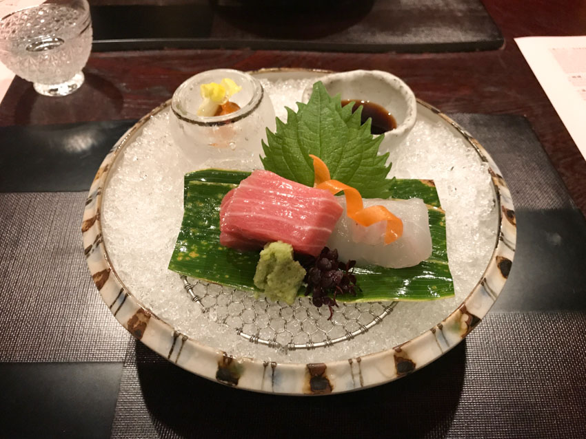 Stone bowl with crushed ice serving as a bed for some raw fish, with a small deep saucer of soy sauce