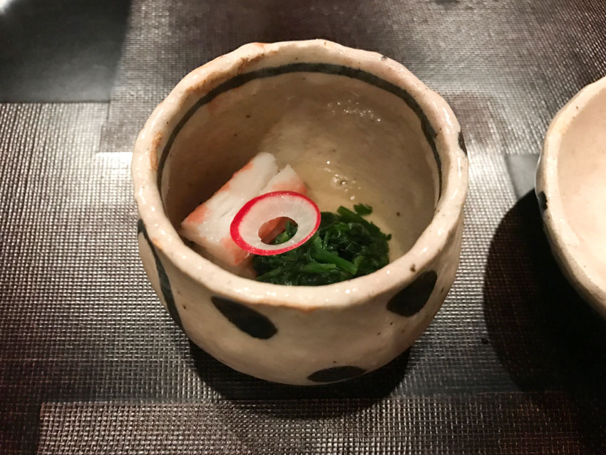A deep small stone bowl with a piece of crab, greens, and a slice of radish