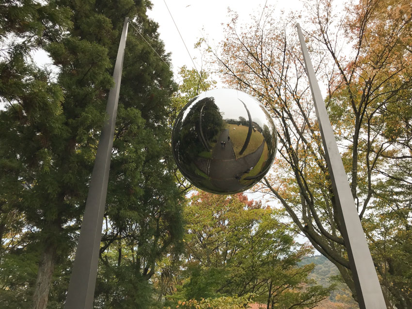 A large metallic sphere suspended between two cables between two poles