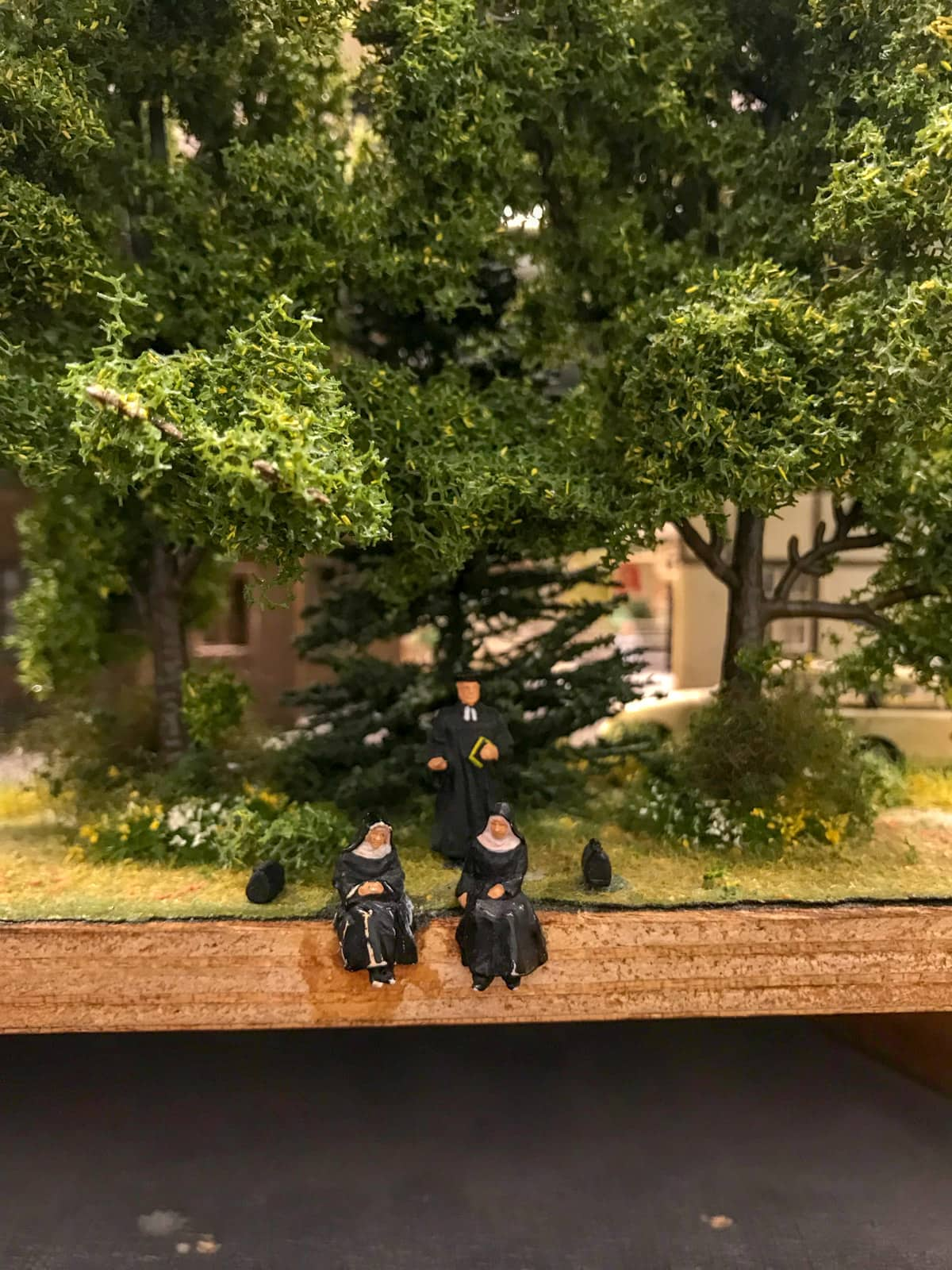 Two figurines of nuns sitting at the edge of a landscape. Behind them is a figurine man dressed in black. There are trees behind them as well