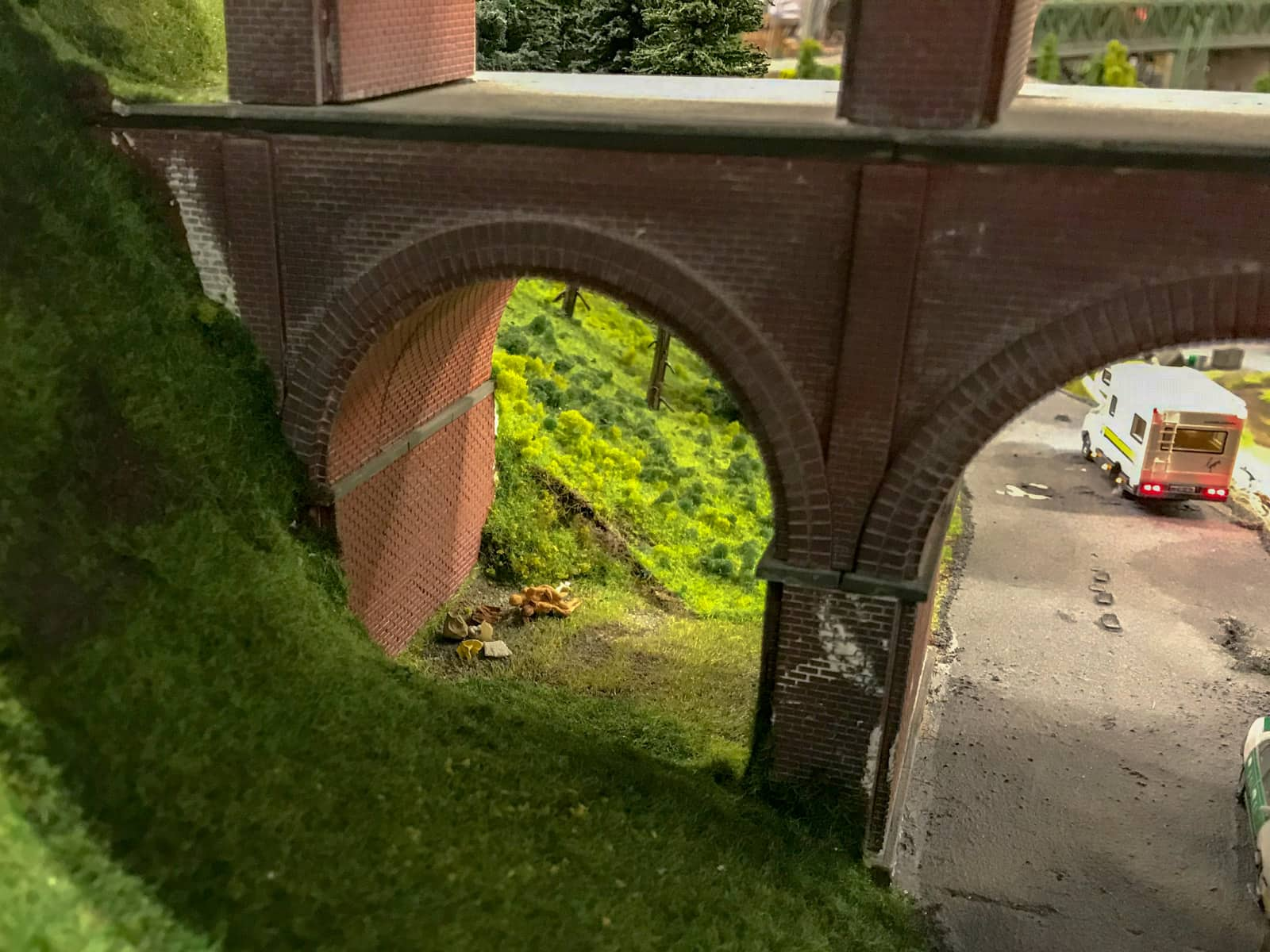 Miniature figurines romping in the grass, under the arches of a bridge