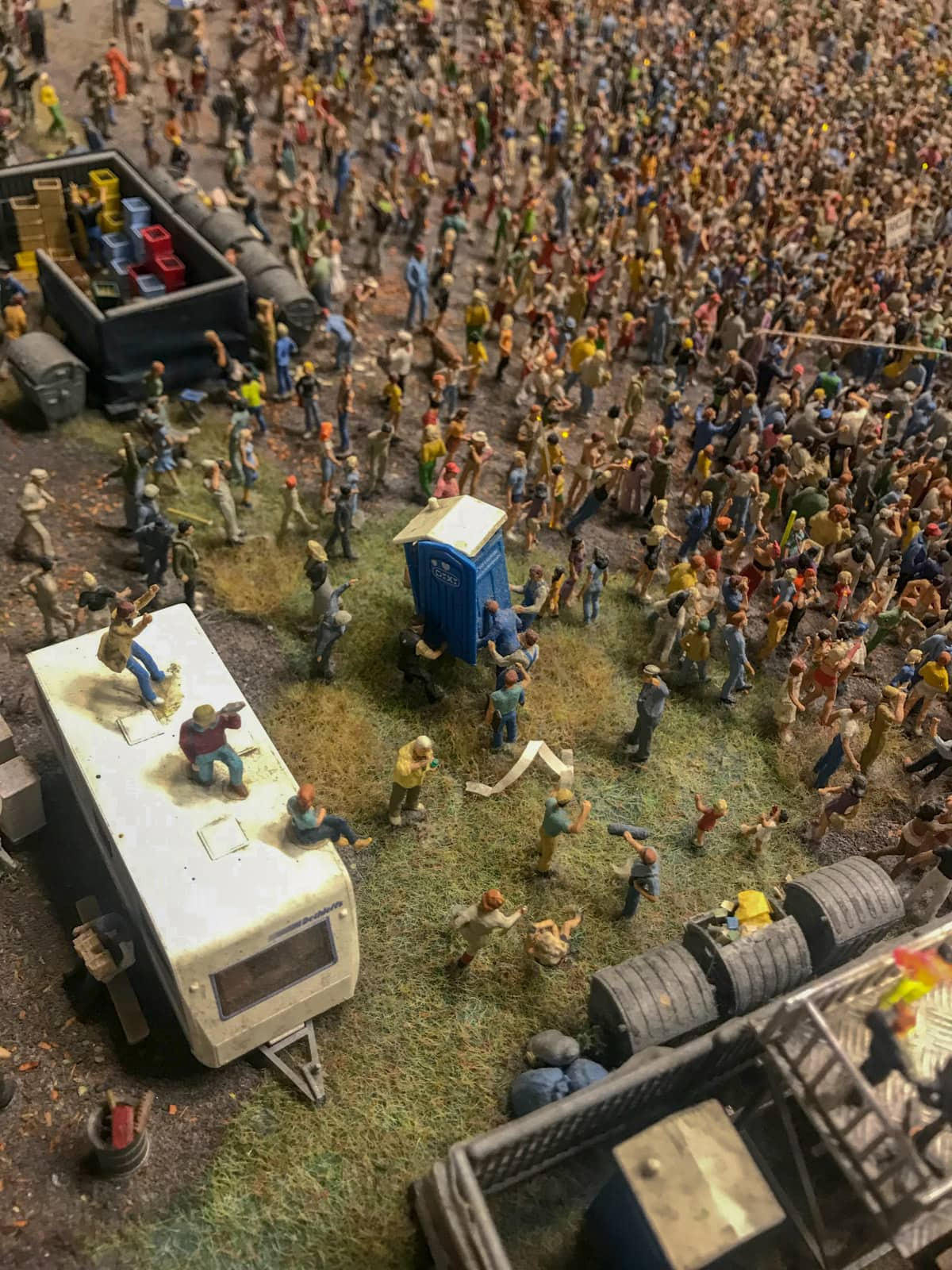 Miniature figurines assembled in a crowd like a festival crowd. There are some figurines carrying a portable toilet