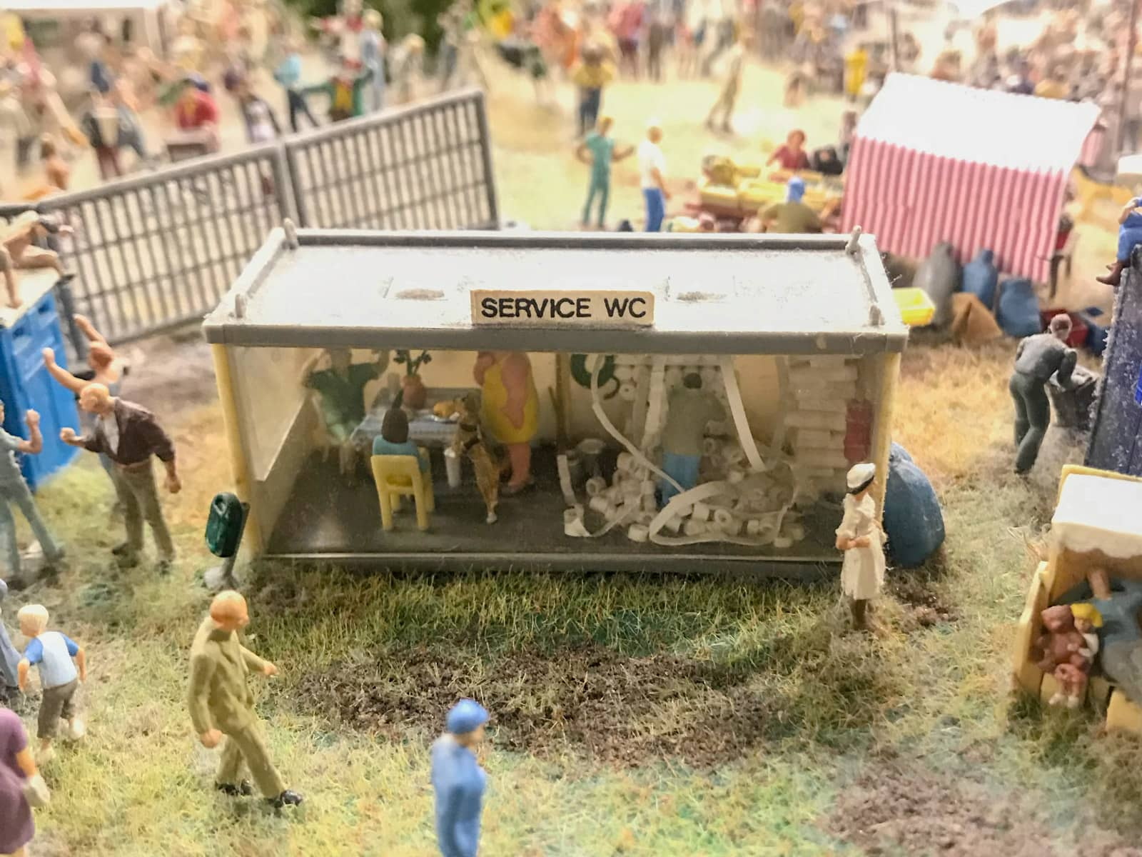 "Miniature figurines inside a glass-walled block called ""Service WC"". There is a figurine man who seems to be dealing with a shelf of toilet paper"