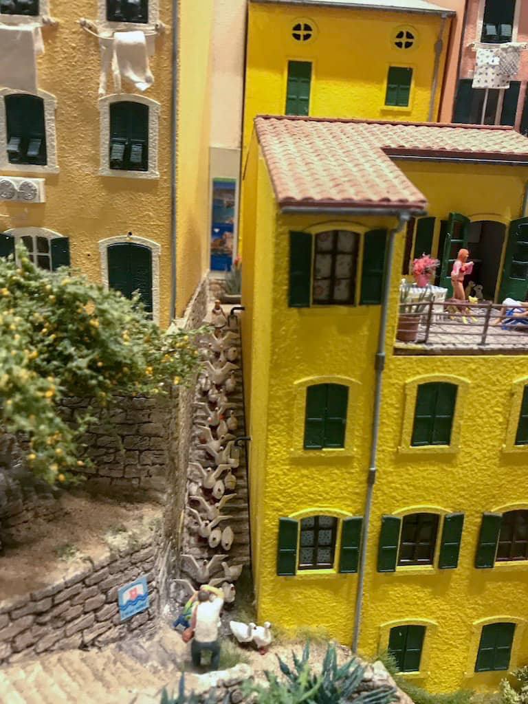 Old Italian-style miniature houses with a long flight of stairs down the side. On the flight of stairs are many miniature seagulls/ducks with a figurine man taking a photo from the bottom of teh stairs.