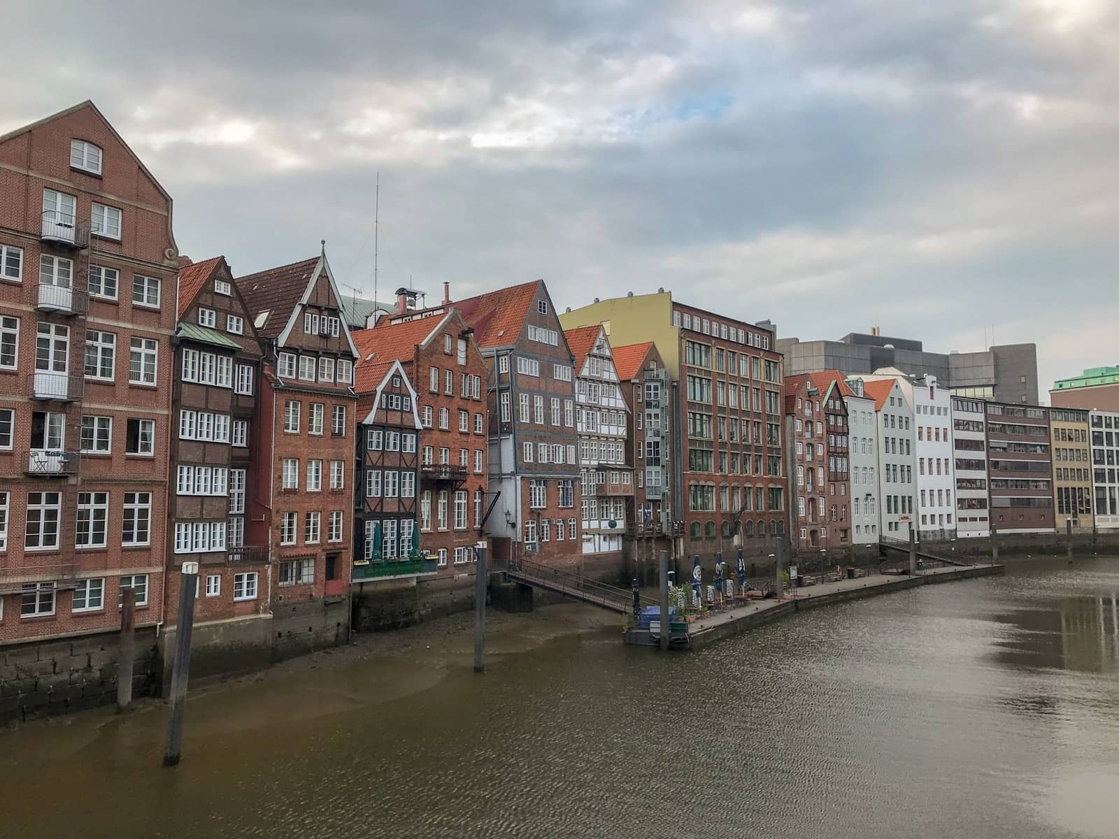 Some large, multi-storey terrace-like houses on the bank of a river, as seen from a distance across the river. It is quite a cloudy day.