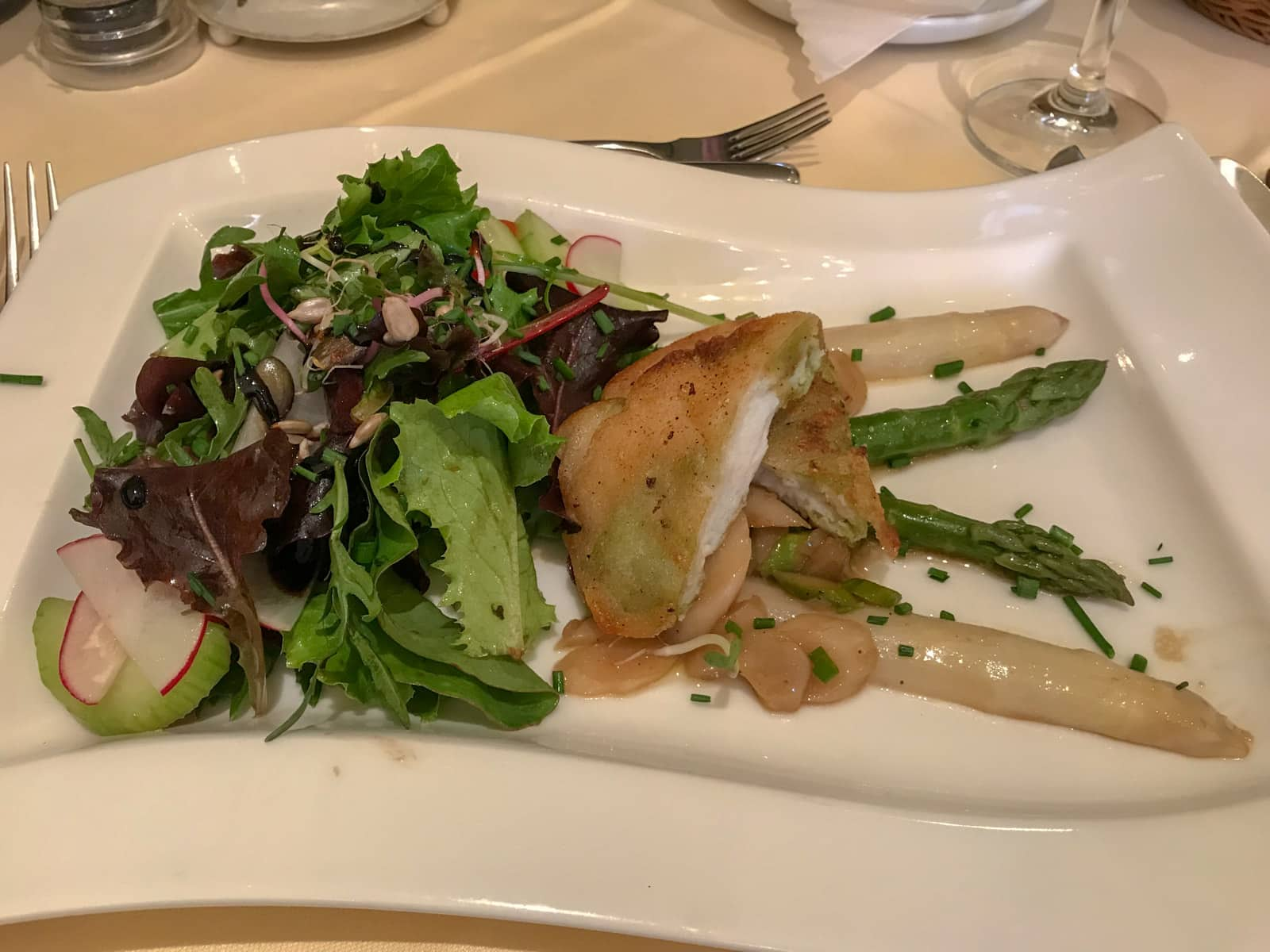 A white, flag-shaped plate on a dining table with salad, asparagus and fish served on it.