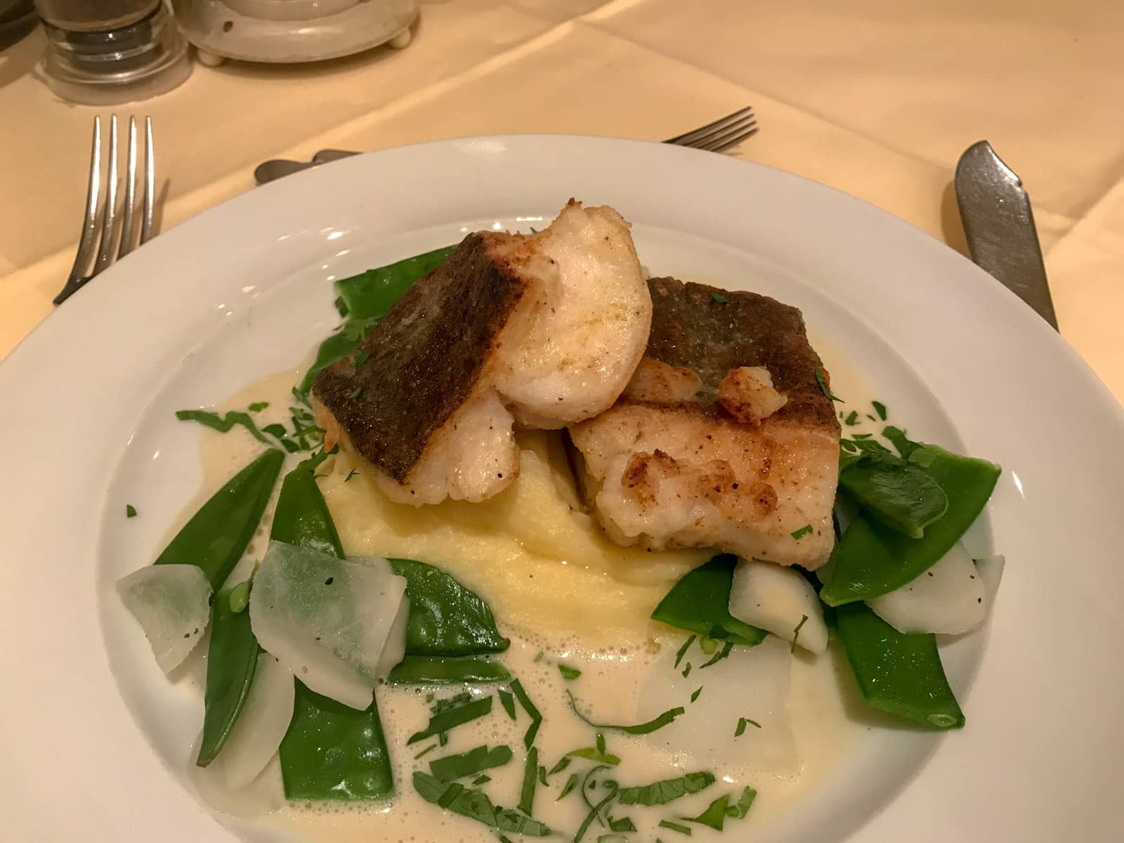 A round white plate with mashed potato, snow peas and fish served on it.