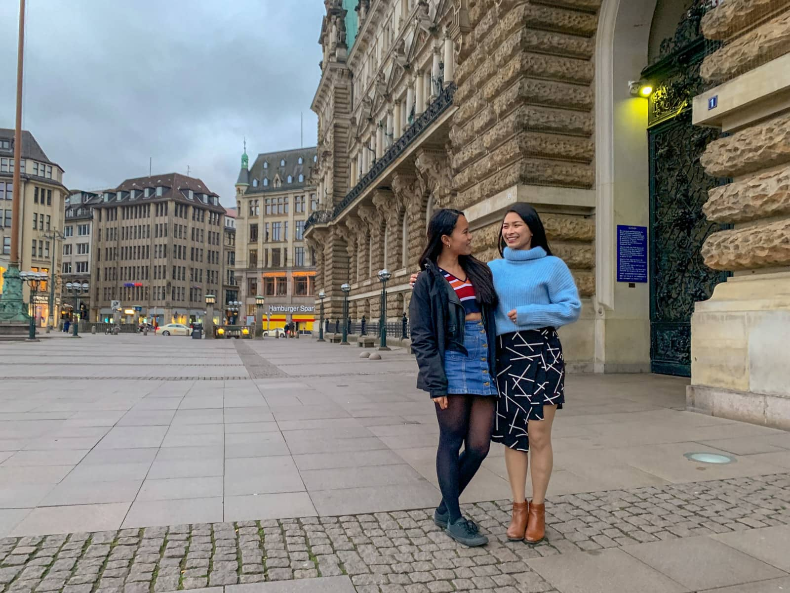Two women smiling, with their arms around each other. Both have dark hair. One is wearing a striped coloured top and a black jacket with a blue skirt, the other is wearing a light blue sweater with a black-and-white patterned skirt. They are in a street setting in Hamburg, Germany