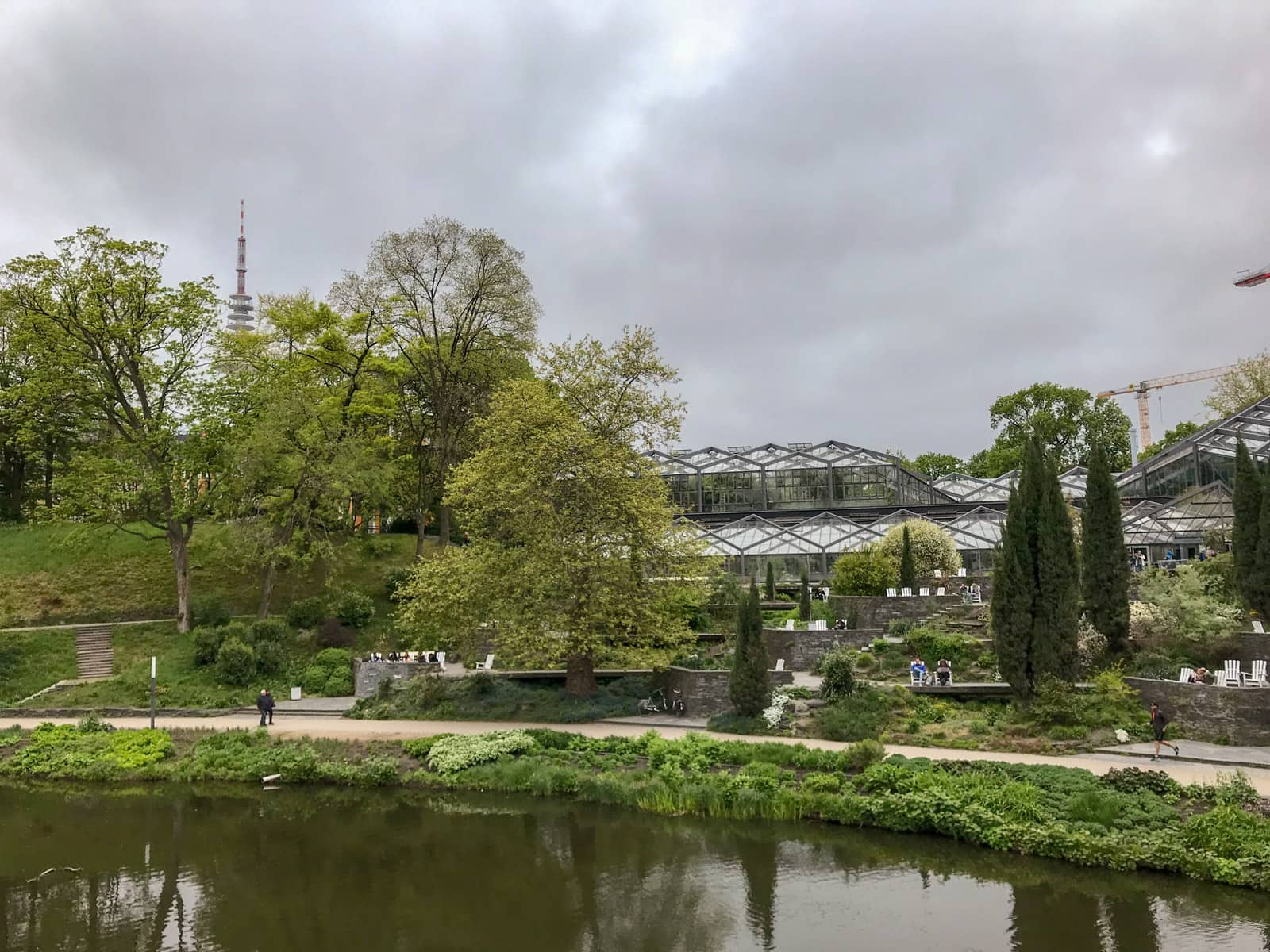 The inside of a park, with a river in the foreground, and greenhouses in the background. There are many trees in the park