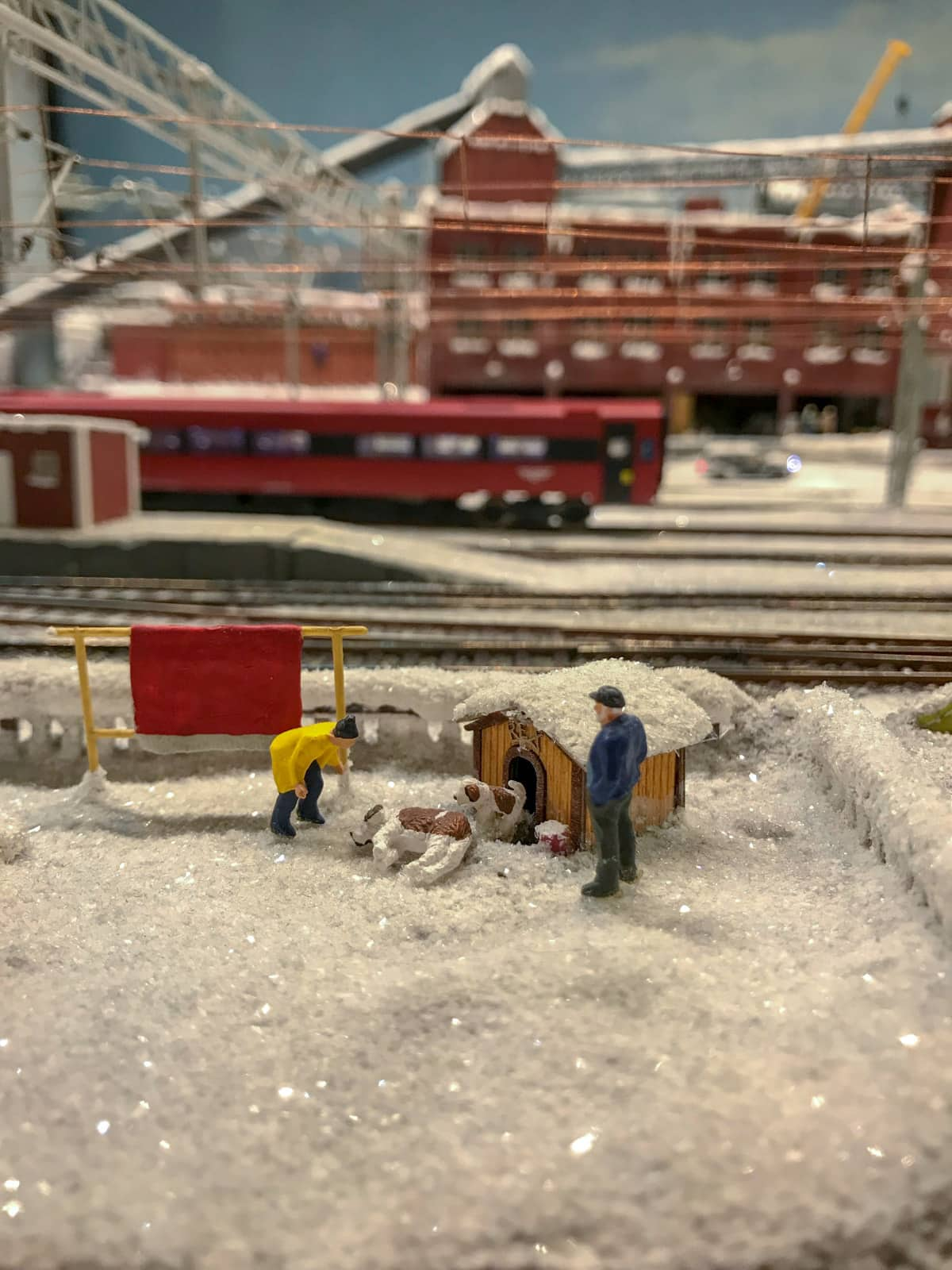 Miniature figurines in a scenario where a man is bending over looking at a dog lying in the snow