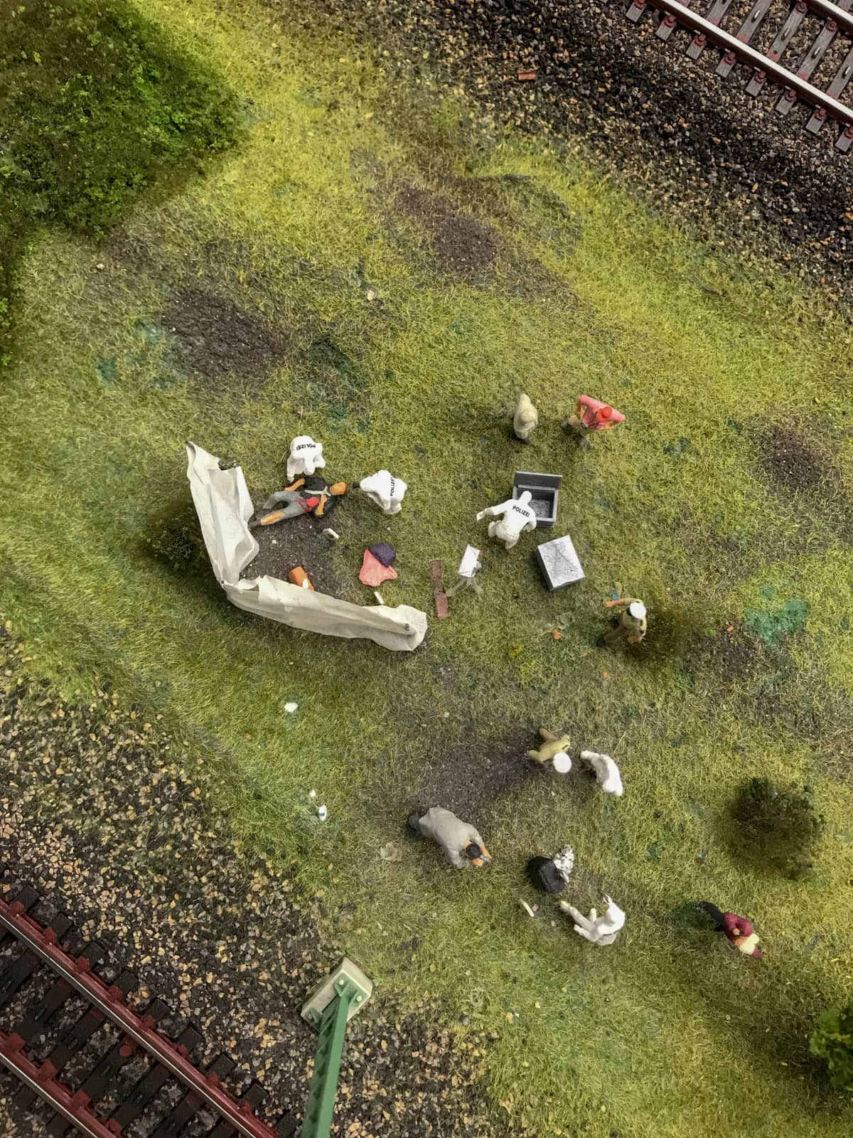 A birds-eye view of figurines near railtracks, assembled with props like a murder scene