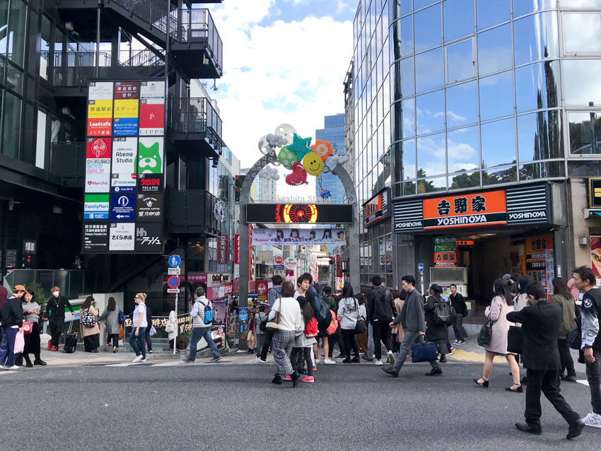 The entrance arch to Takeshita Street, with many pedestrians walking. On the left, there is a building with a metal staircase, and stairs leading downwards, and on the right, a glass high-rise building and a Yoshinoya restaurant