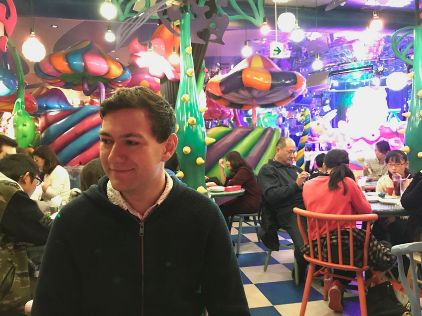 Nick looking off-camera, in a restaurant setting with a black-and-white checkered floor and colourful decor, some resembling big trees and others looking like toadstools