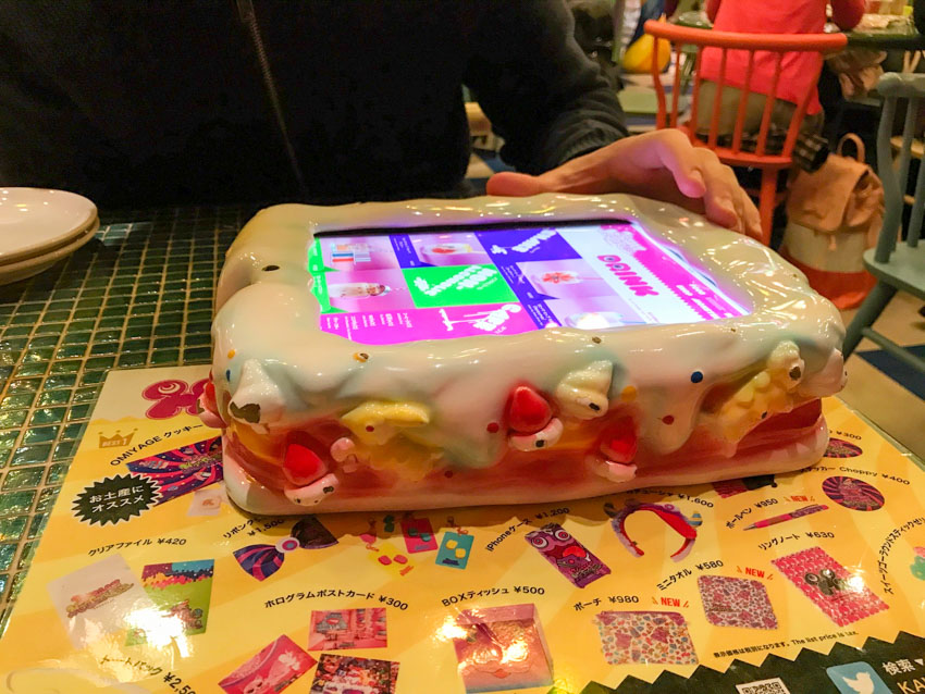 A large plastic rectangular cake with a digital screen on top, resembling an iPad