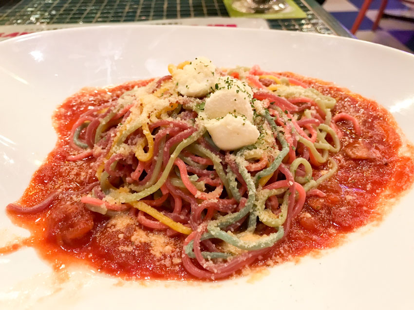 Colourful spaghetti with grated cheese and red tomato pasta sauce on a white plate