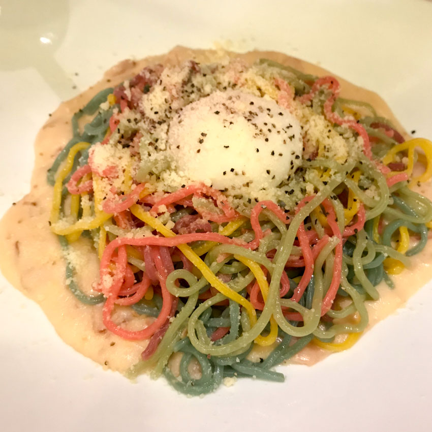 Colourful spaghetti with grated cheese and white pasta sauce on a white plate