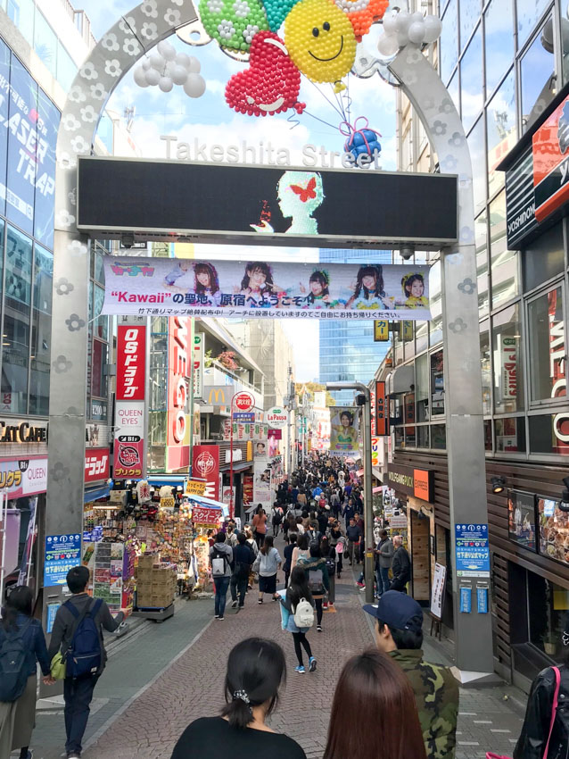 The entrance arch to a busy street, called Takeshita Street. The arch has a banner hanging towards the top, an LED screen with advertisements, and colourful balloons creating a smiley shape and heart shape at the top of the arch