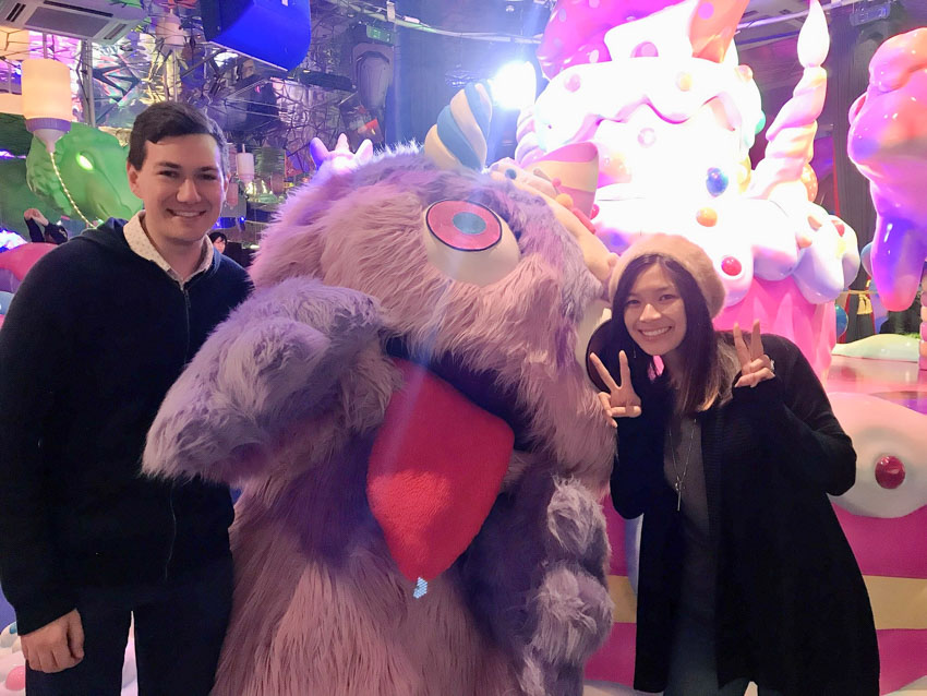 Me and Nick, smiling, standing on either side of someone dressed in a giant fluffy light purple monster costume. The monster has a large tongue and big eyes. I am making two peace signs with my hands.