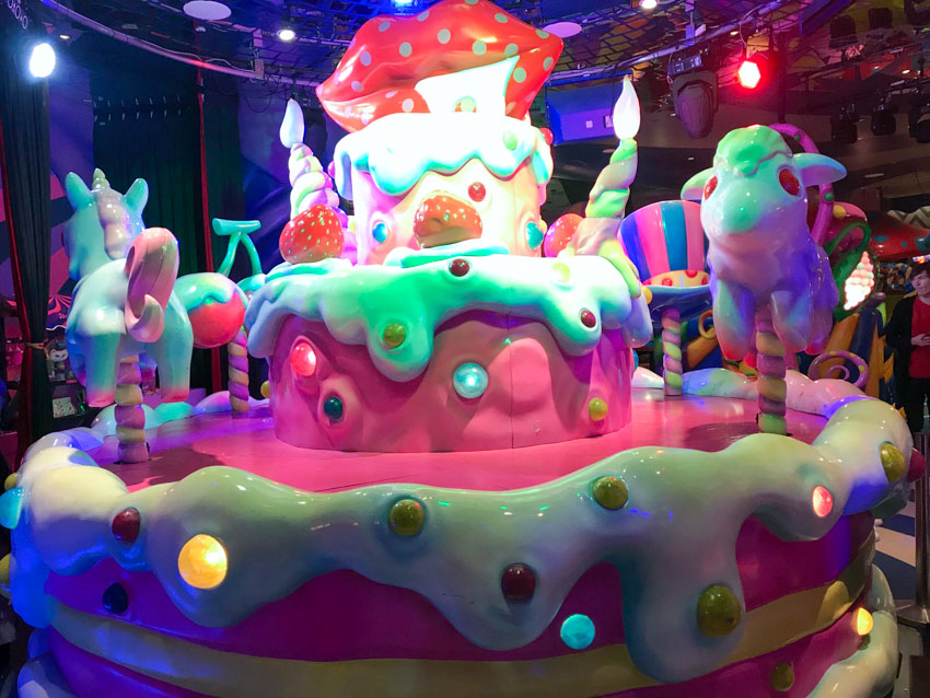 A sculpture made from what appears to be shiny plastic, resembling a cake with thick icing and horses like a carousel. Round coloured lights on the sculpture and hanging above the sculpture light it up
