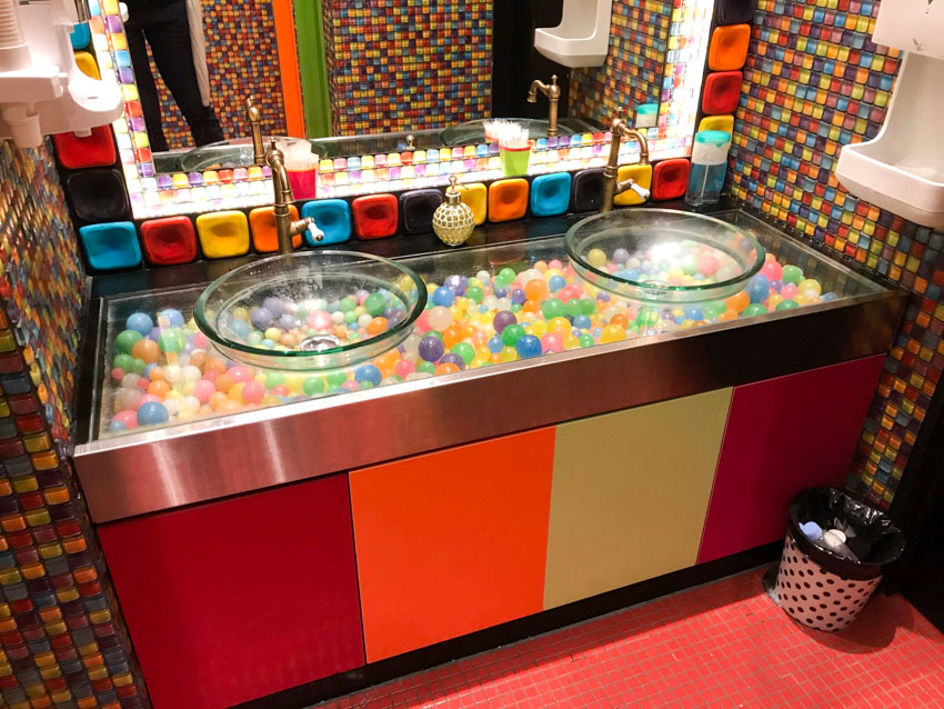 Two basins in front of a mirror, bordered by giant colourful tiles. The basins are transparent, revealing colourful balls sitting in a bed underneath.