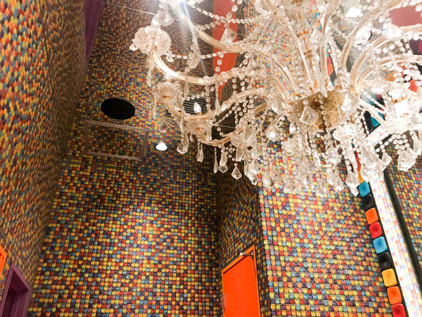 Walls in a bathroom covered with clourful square tiles, with a classic chandelier hanging from the ceiling.