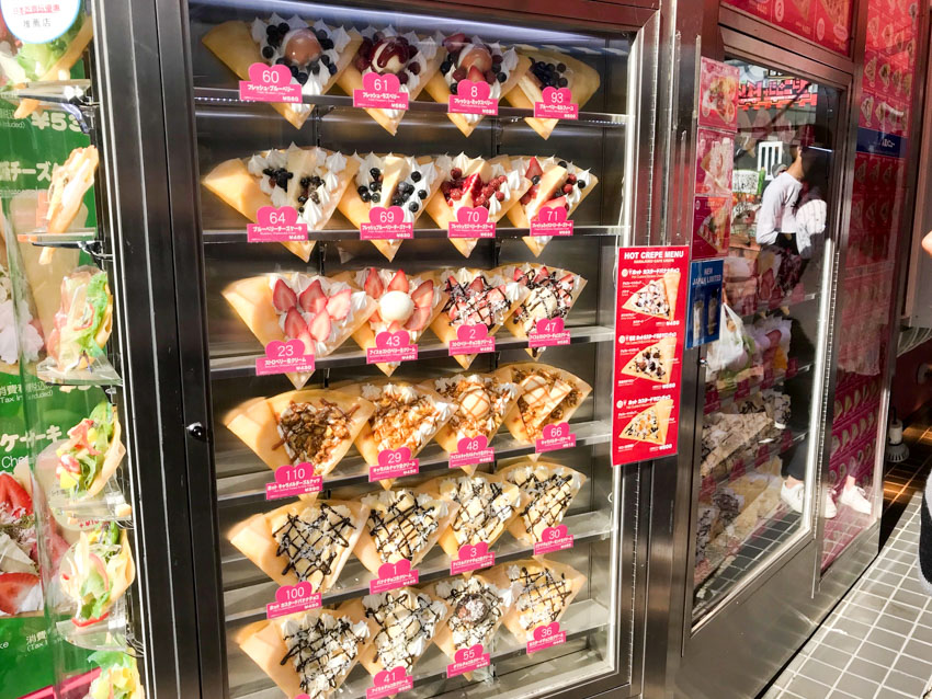 Many fake plastic crepes on display in a glass store front, indicating various flavours