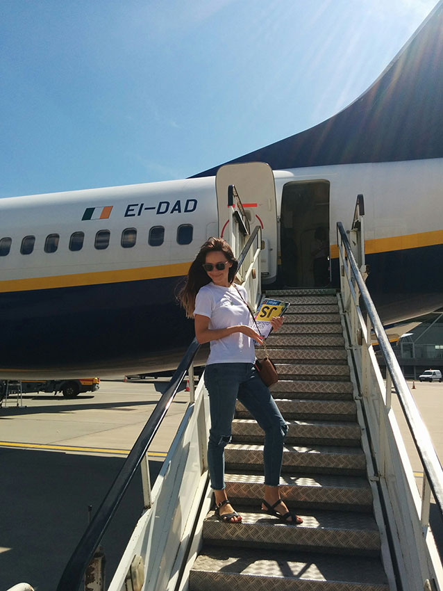 Amy on the steps to a plane, travelling with her JavaScript books
