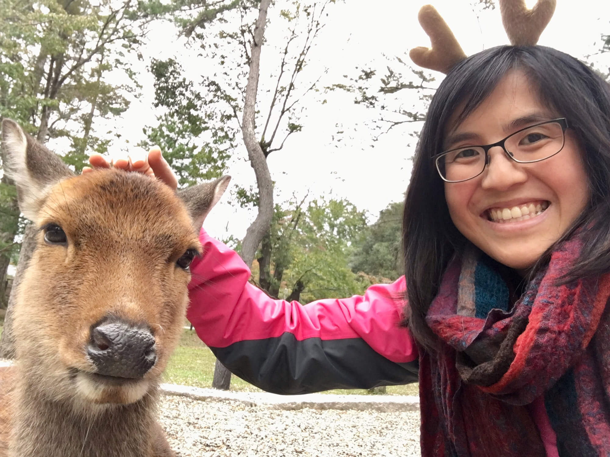 A woman with glasses, smiling and patting a deer