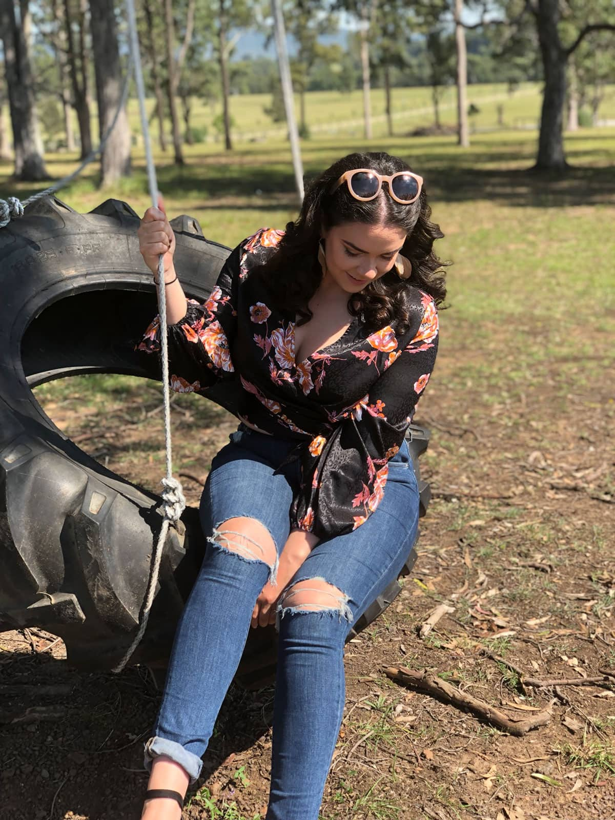 A woman with curly dark hair, wearing blue ripped jeans and a black floral blouse sitting on a tyre swing