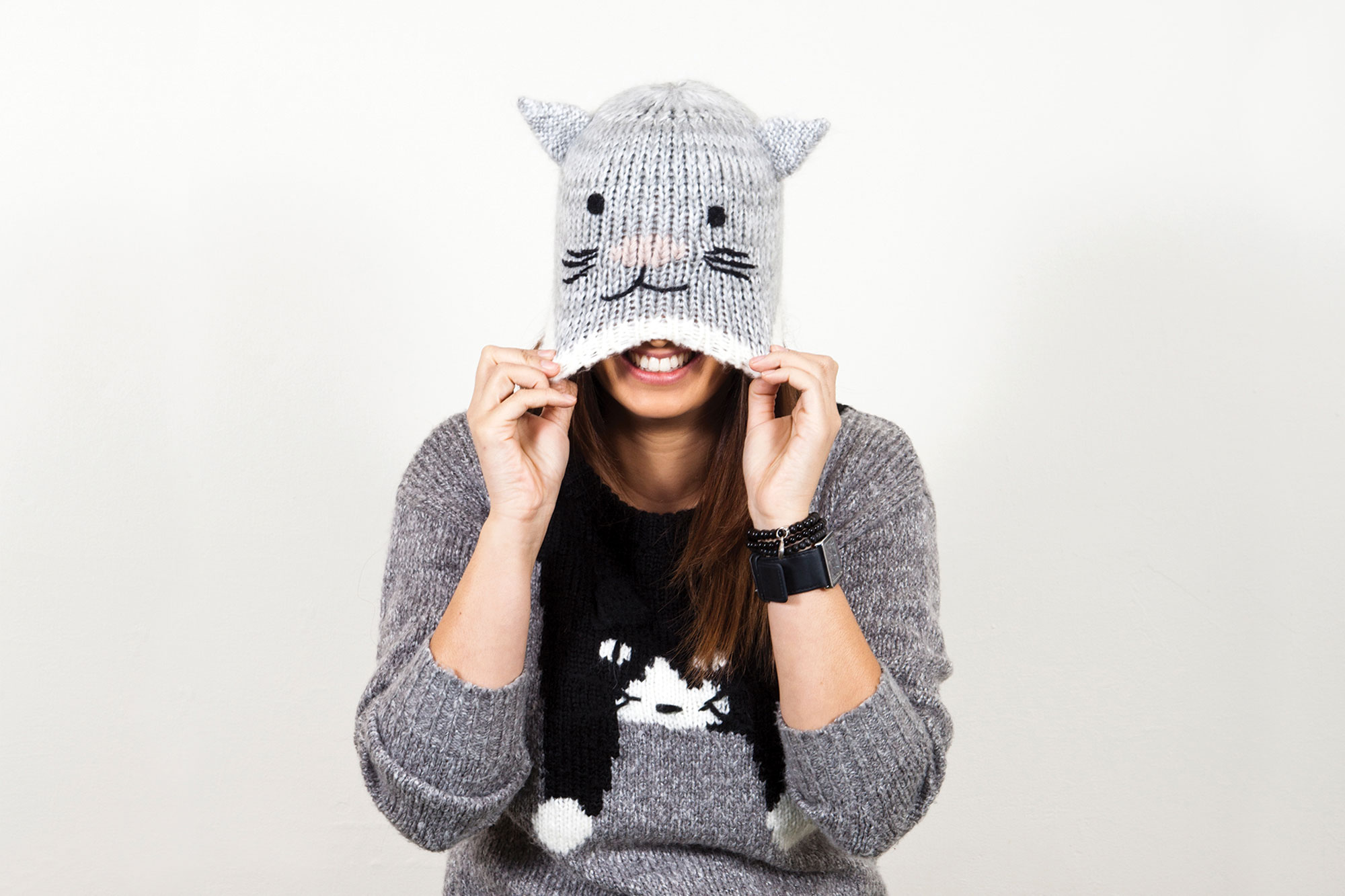 Kylie, wearing a grey sweater with a cat image down the front, and a light grey cat shaped beanie pulled over her eyes with her hands. She is grinning.