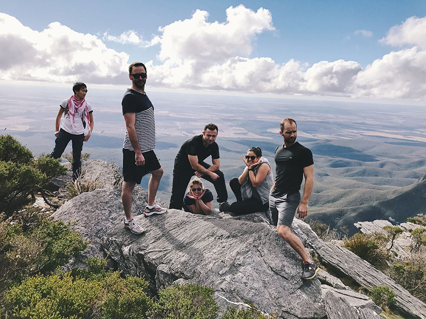 Six people atop a rocky mountain, in various different poses. The sky is blue and has quite a lot of white clouds.