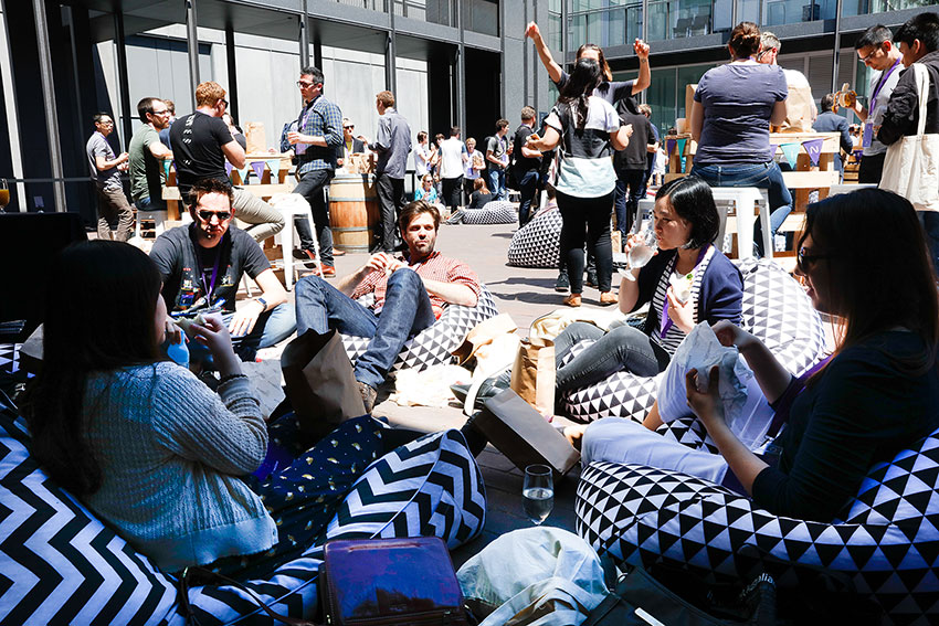 People sitting on black-and-white patterned beanbags, eating and drinking. Many people in the background conversing and eating as well.