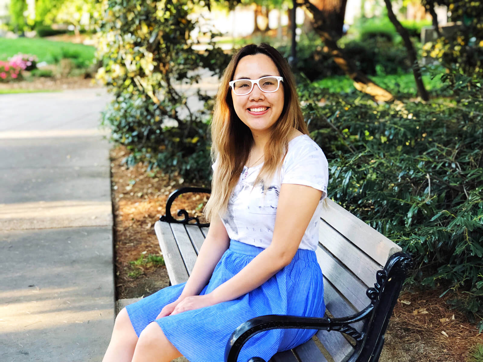 A girl sitting on a park bench, smiling. She has dark hair with blonde highlights, is wearing white glasses, and a light coloured top and a blue skirt.
