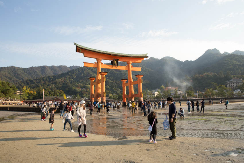 The shrine with a lot of people walking around in the wet sand
